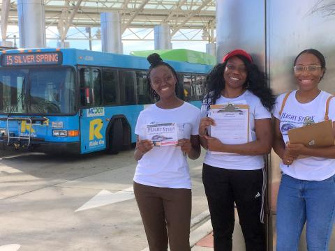 Jariatu, Faith and Aliyah, PLIGHT Study researchers, conducting transit stop interviews at the Langley Park Transit Center, July 1, 2019.