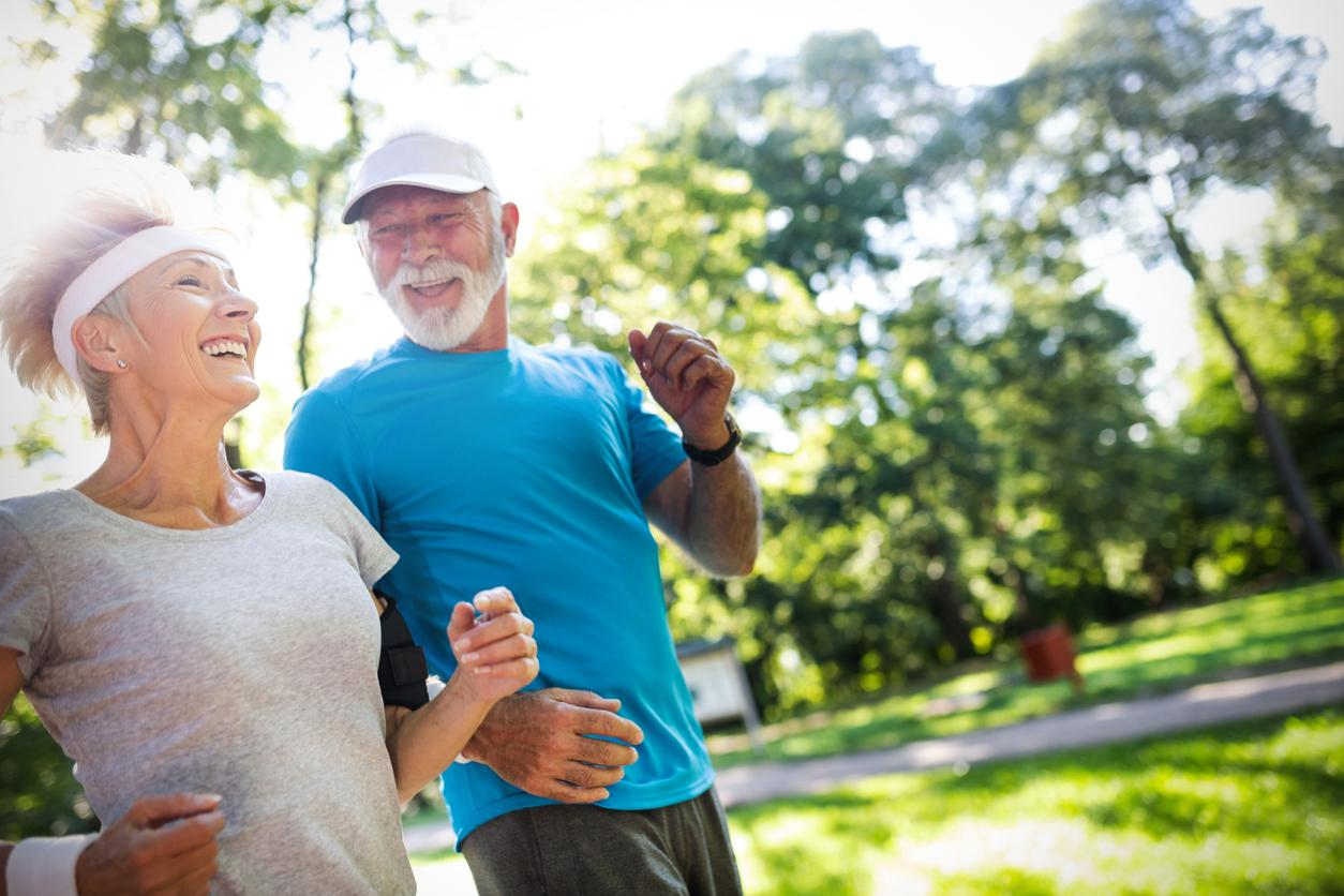 Older white couple running outside and smiling