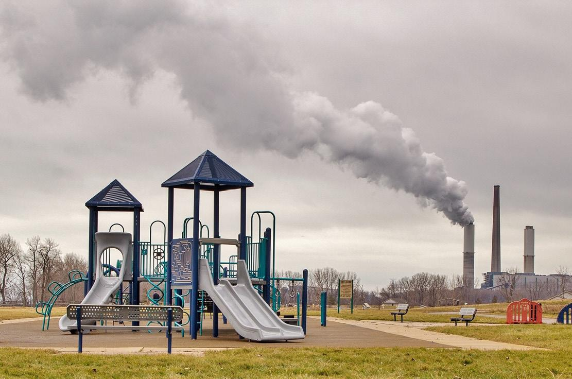Playground With Factory Smokestack Billowing Pollution In The Background