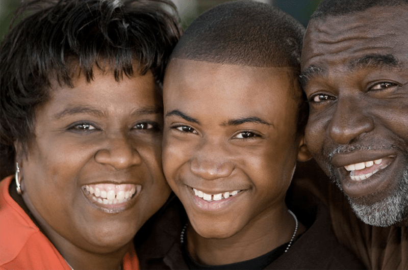 Close up photo of Black woman, boy and man smiling with their heads close together