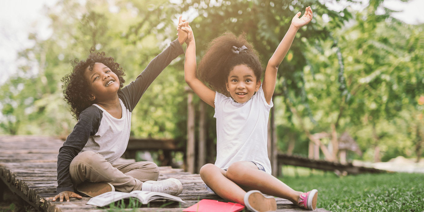 Two Black children sit outside during summer looking happy with arms in the air